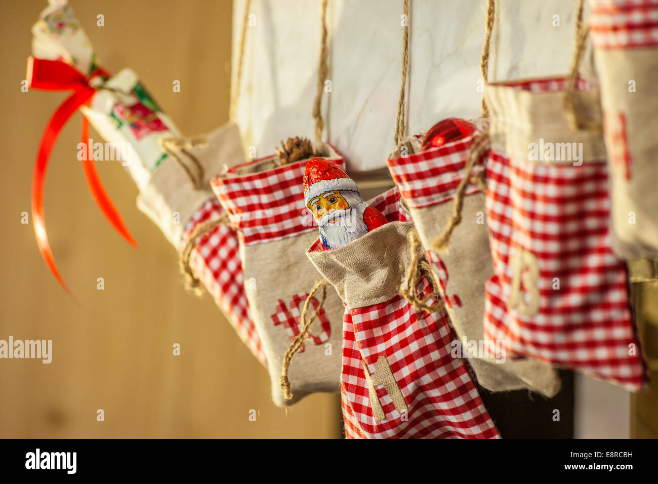 Bags of an advent calendar hanging on the fireplace - Stock Image
