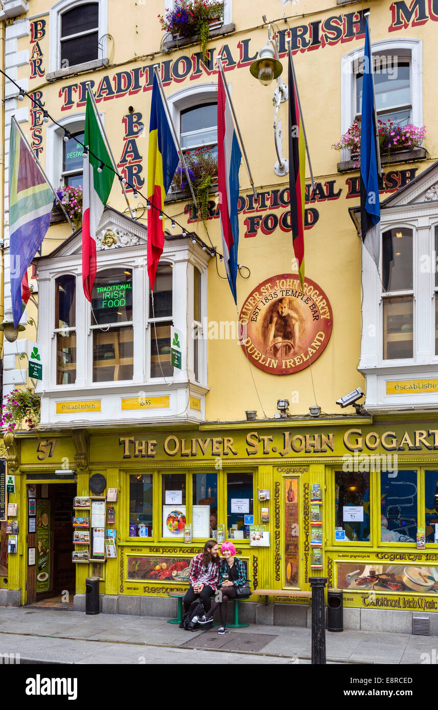 Young couple siting outside The Oliver St John Gogarty pub on Temple Bar in the city centre, Dublin City, Republic - Stock Image