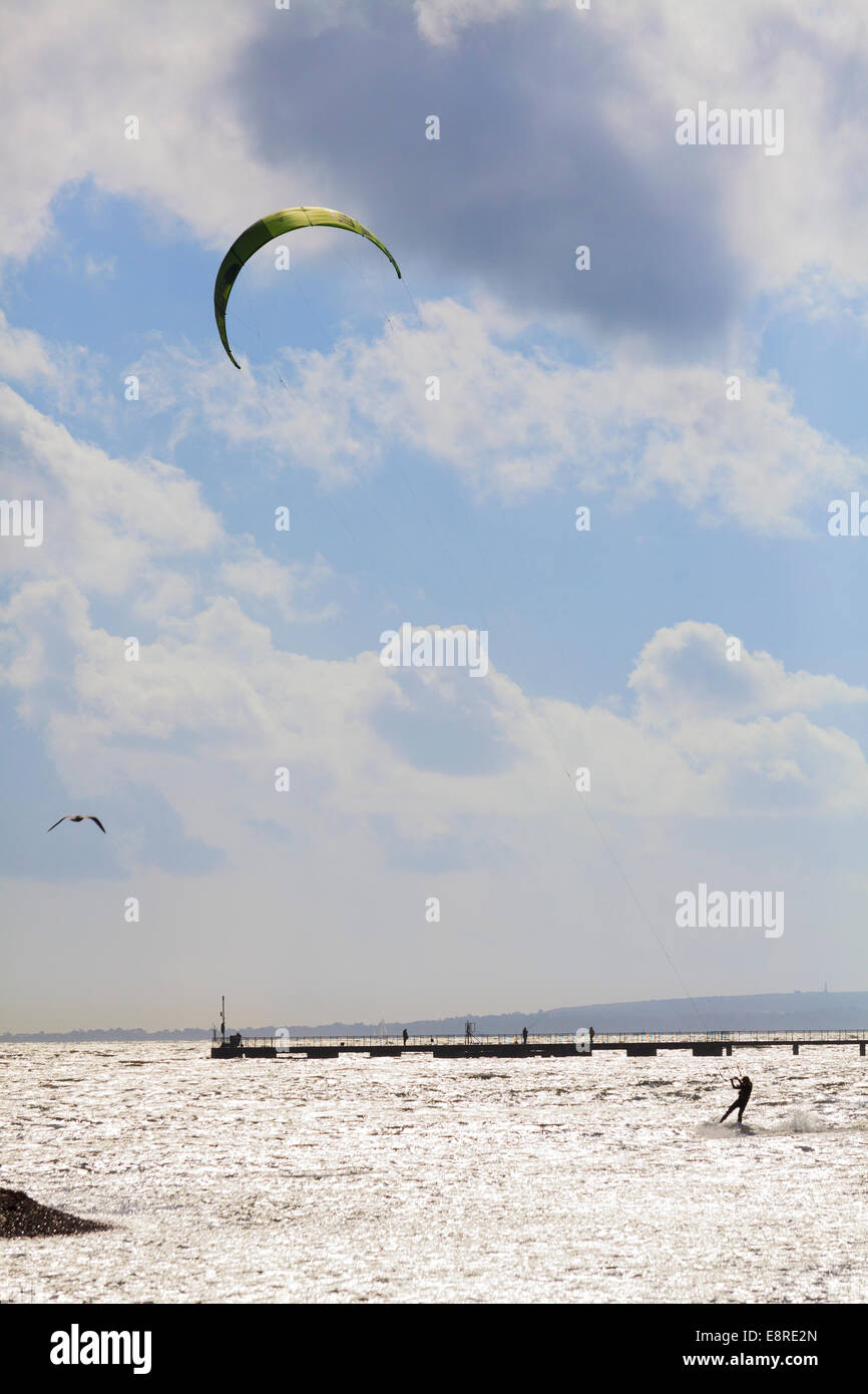 Person kitesurfing in harbour on semi silhouette against sparkling sea. - Stock Image