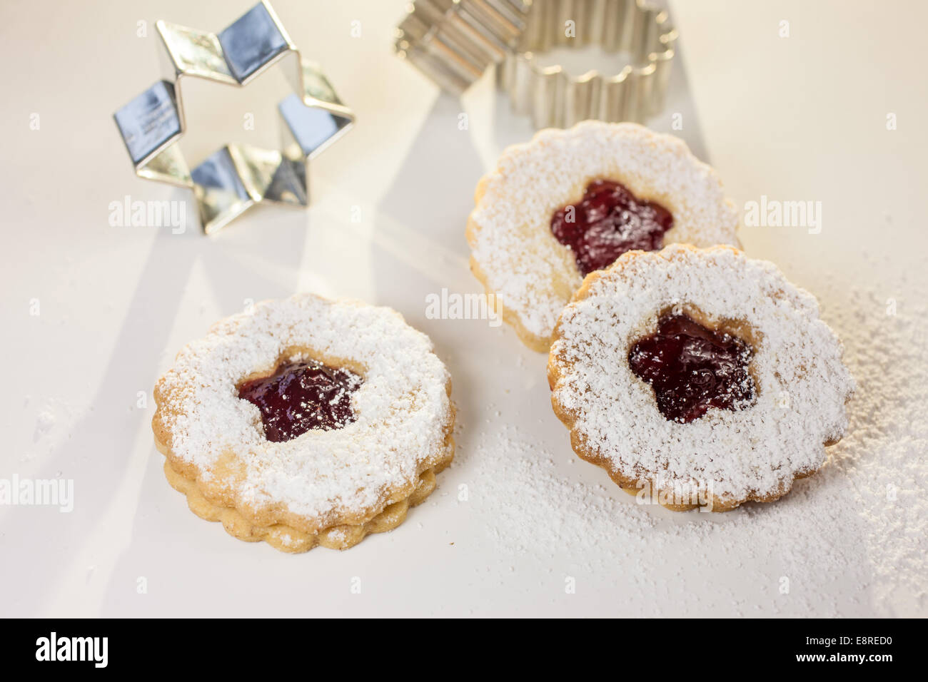 Christmas cookies and cookie cutters on white table - Stock Image