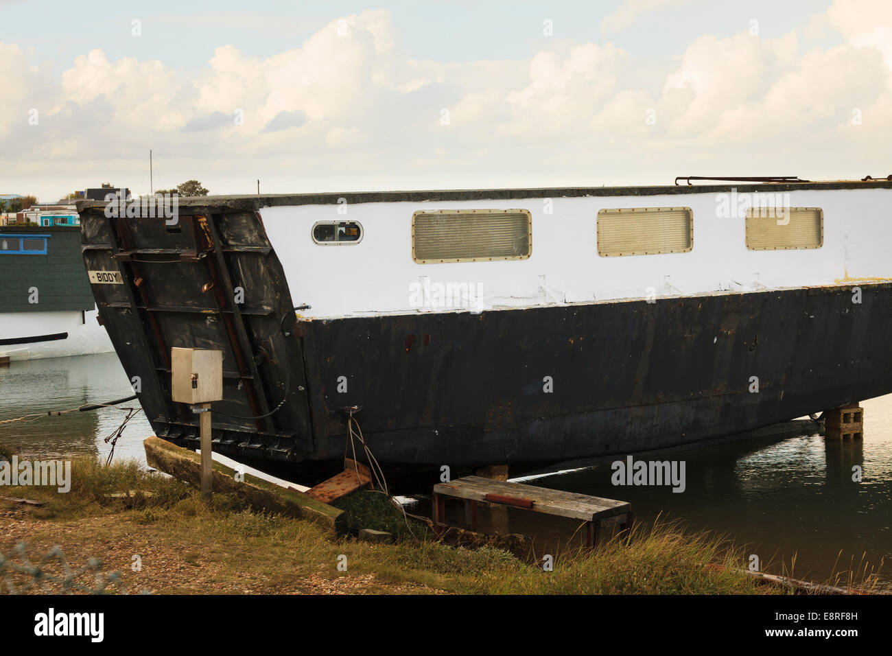 Old landing craft converted into houseboat. - Stock Image