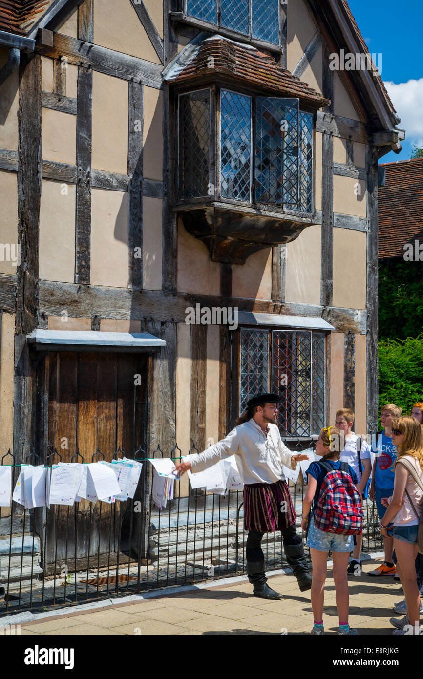 Shakespearean actor guiding a tour group of school kids below Wm Shakespeare home in Stratford Upon Avon, Warwickshire, - Stock Image