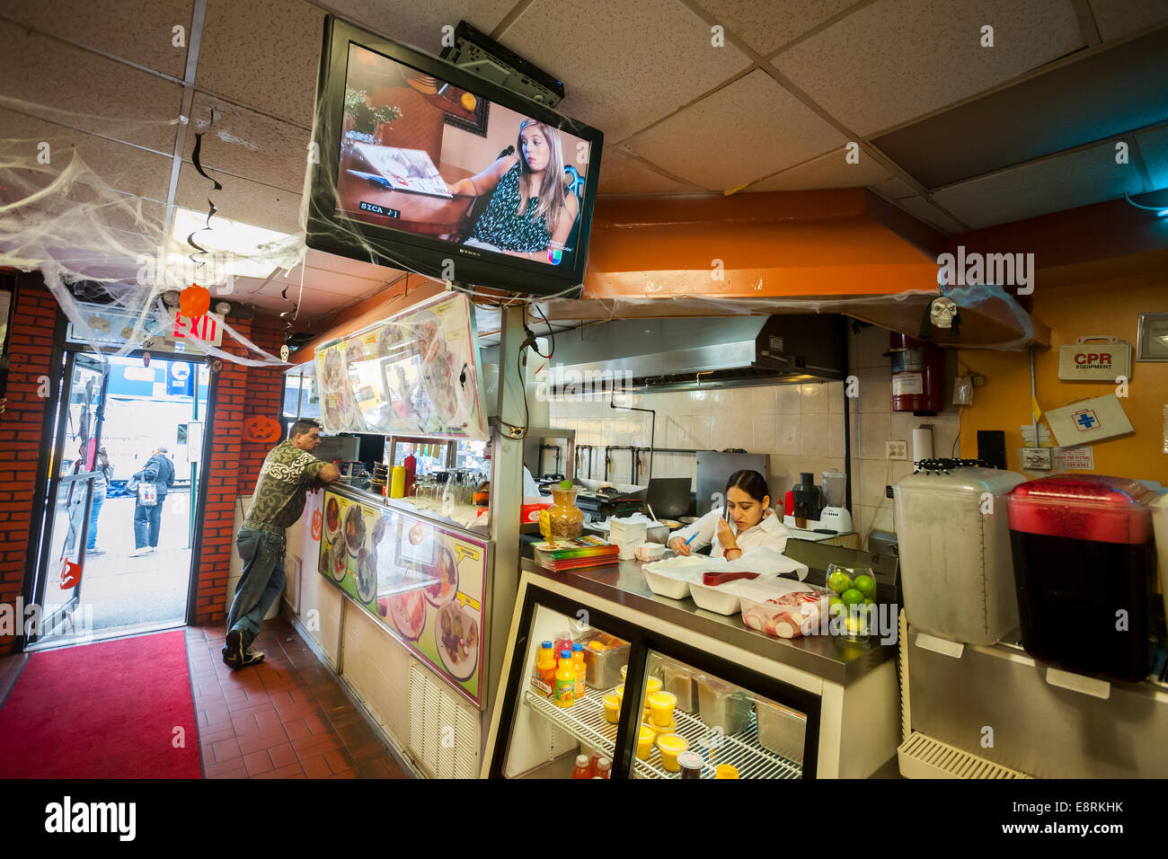 Telenovelas (Hispanic soap operas) play on a television in an Hispanic restaurant in the community of Jackson Heights - Stock Image