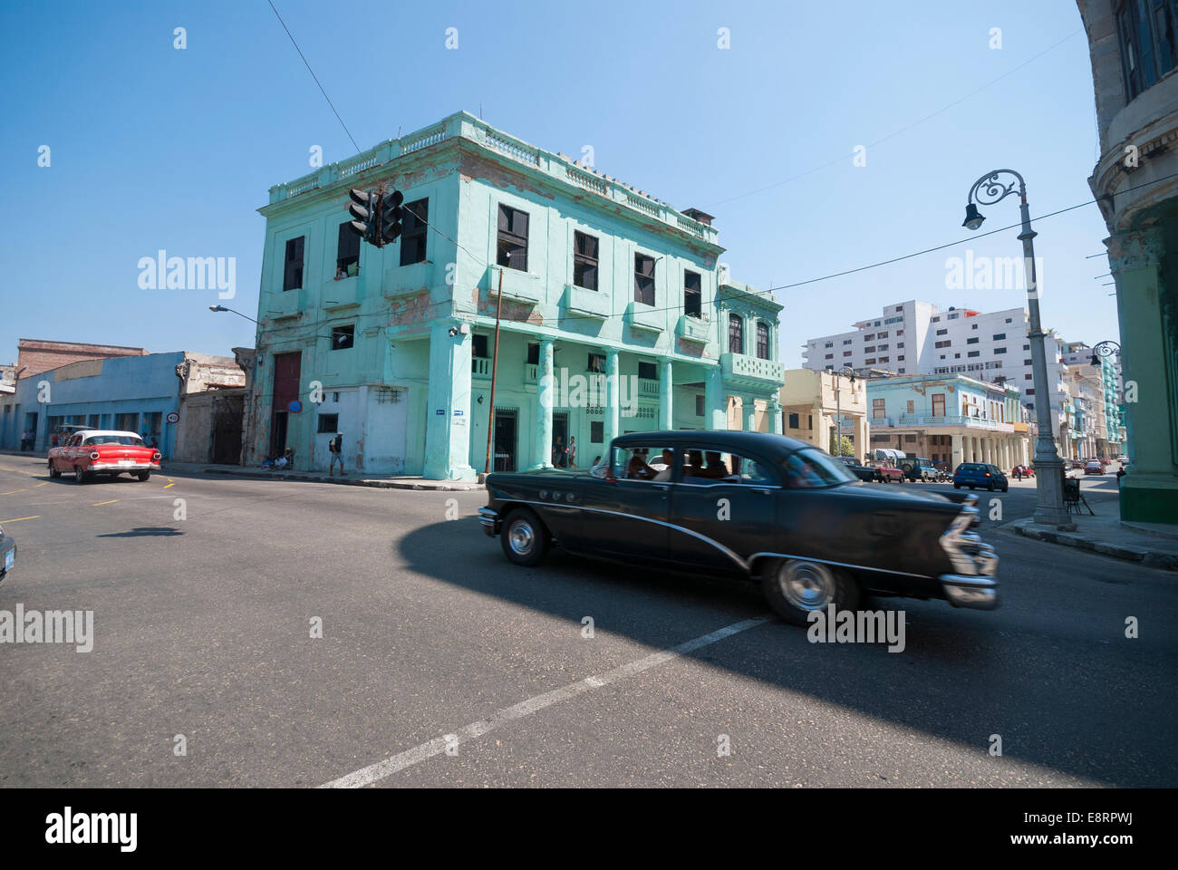 Two vintage American cars speed through an intersection in a central Havana neighborhood. Stock Photo