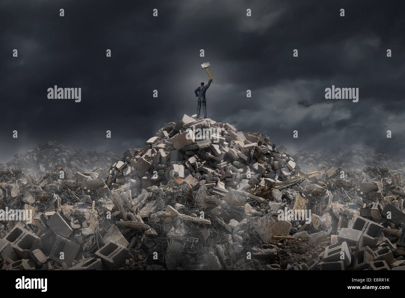 Destroy and demolish concept as a businessman  standing on a mountain of  building ruins holding a sledge hammer - Stock Image