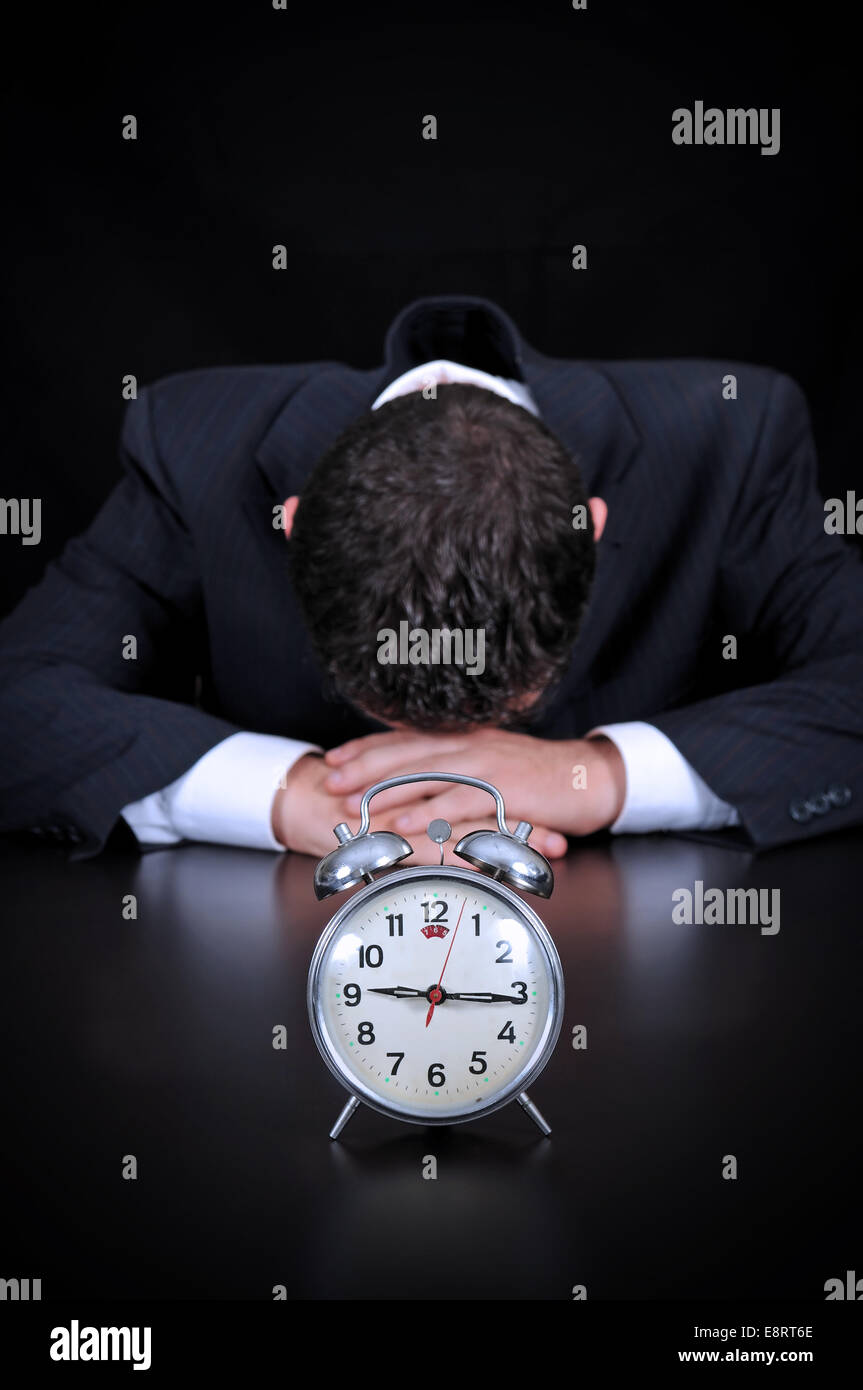 Businessman is wasting time concept on the black background - Stock Image