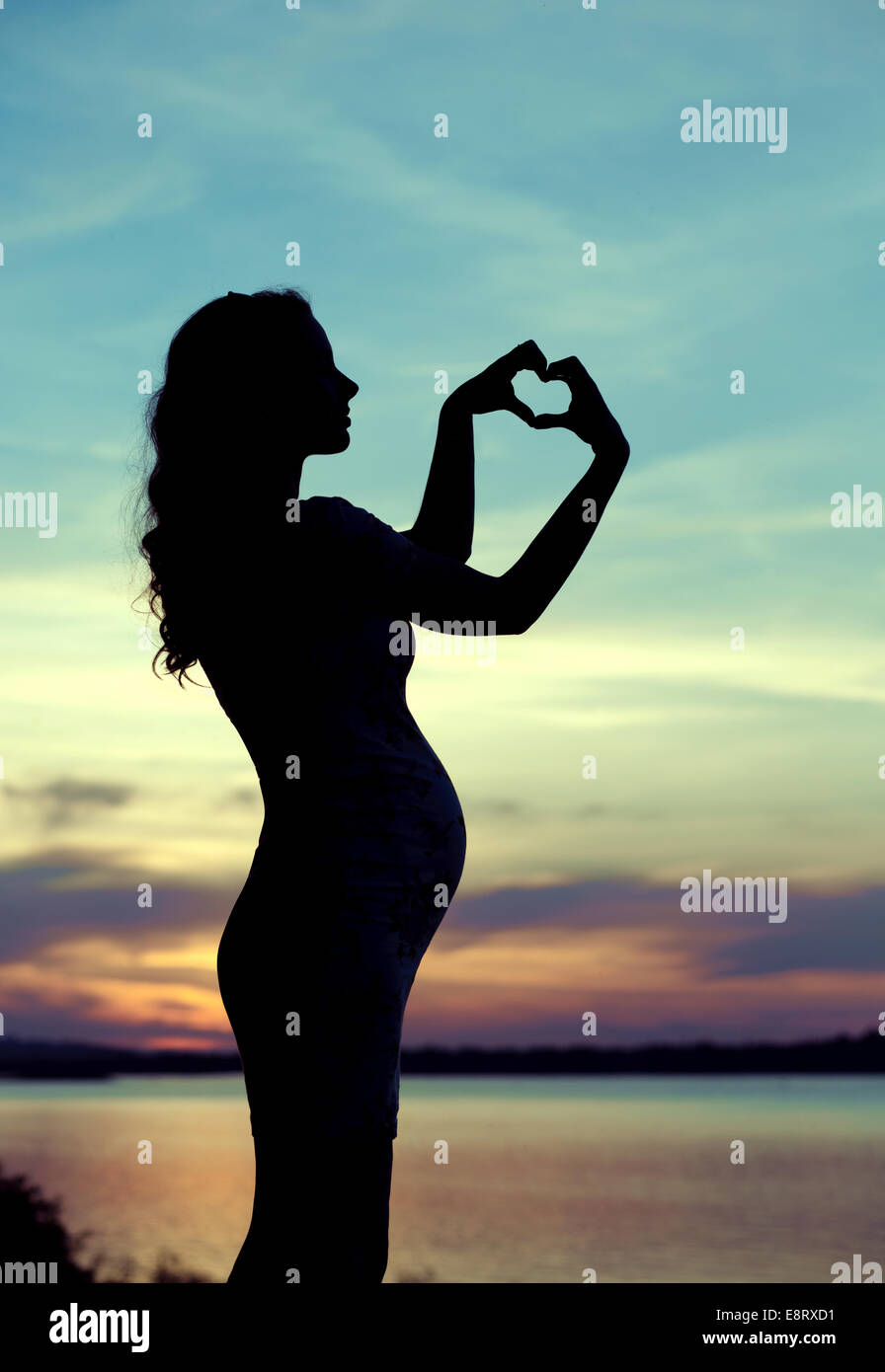 Pregnant mother making the heart sign - Stock Image