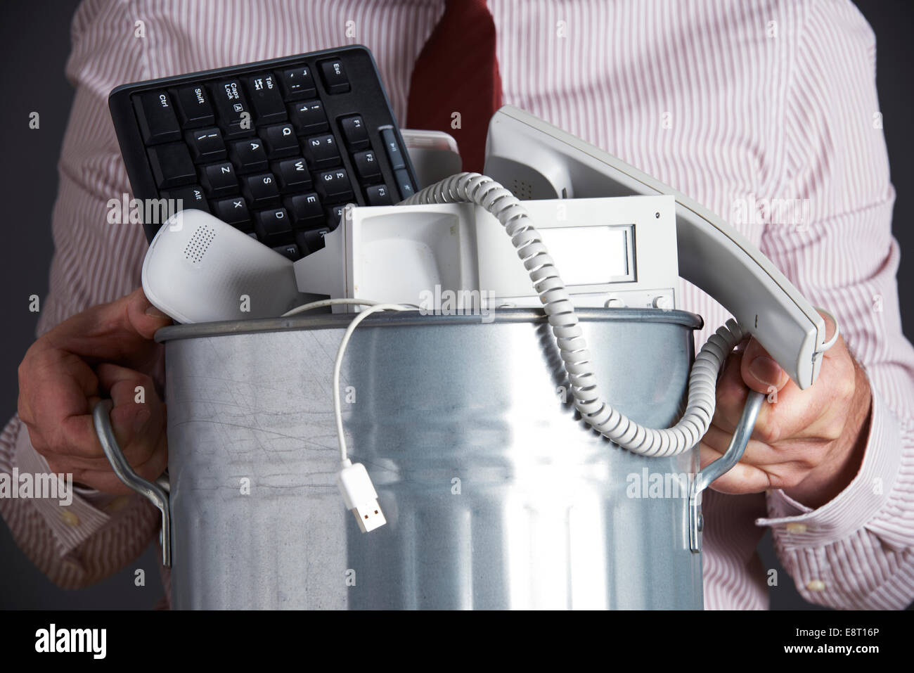 Businessman Holding Garbage Can With Obsolete Office Equipment - Stock Image