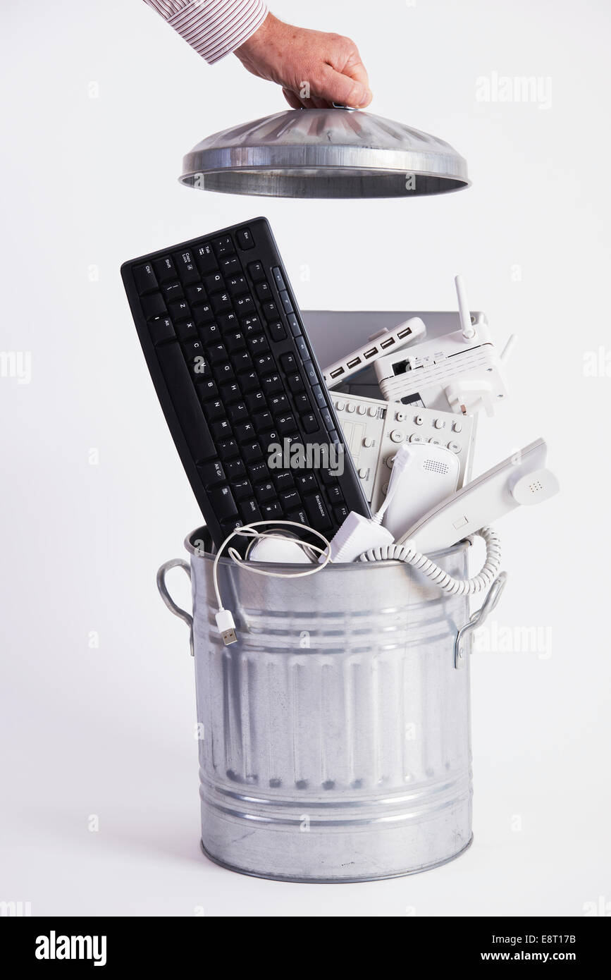 Businessman Filling Garbage Can With Obsolete Office Equipment - Stock Image