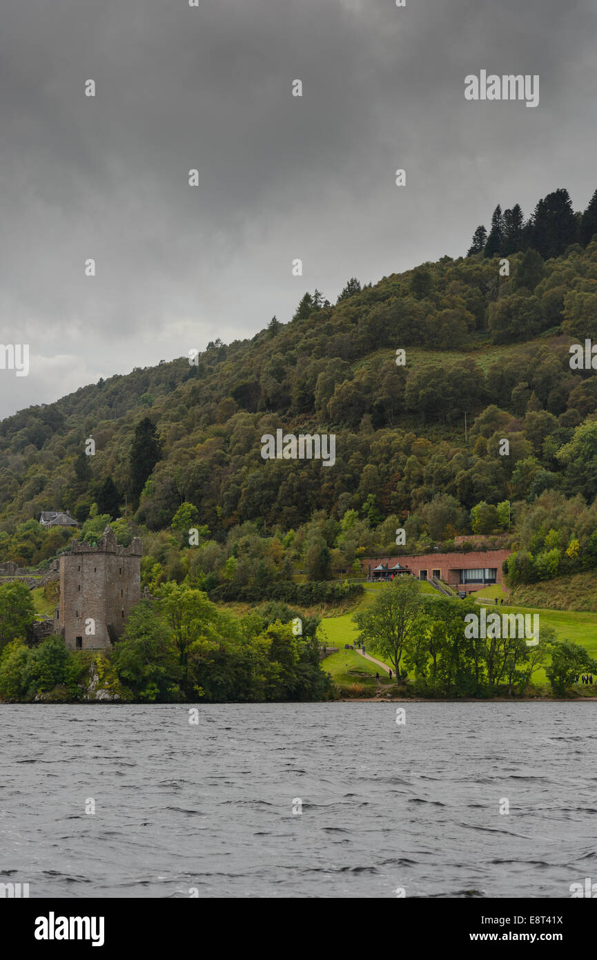 Urquhart Castle, a historical ruin ruins on the banks of Loch Ness with the Visitor Centre Center behind. - Stock Image