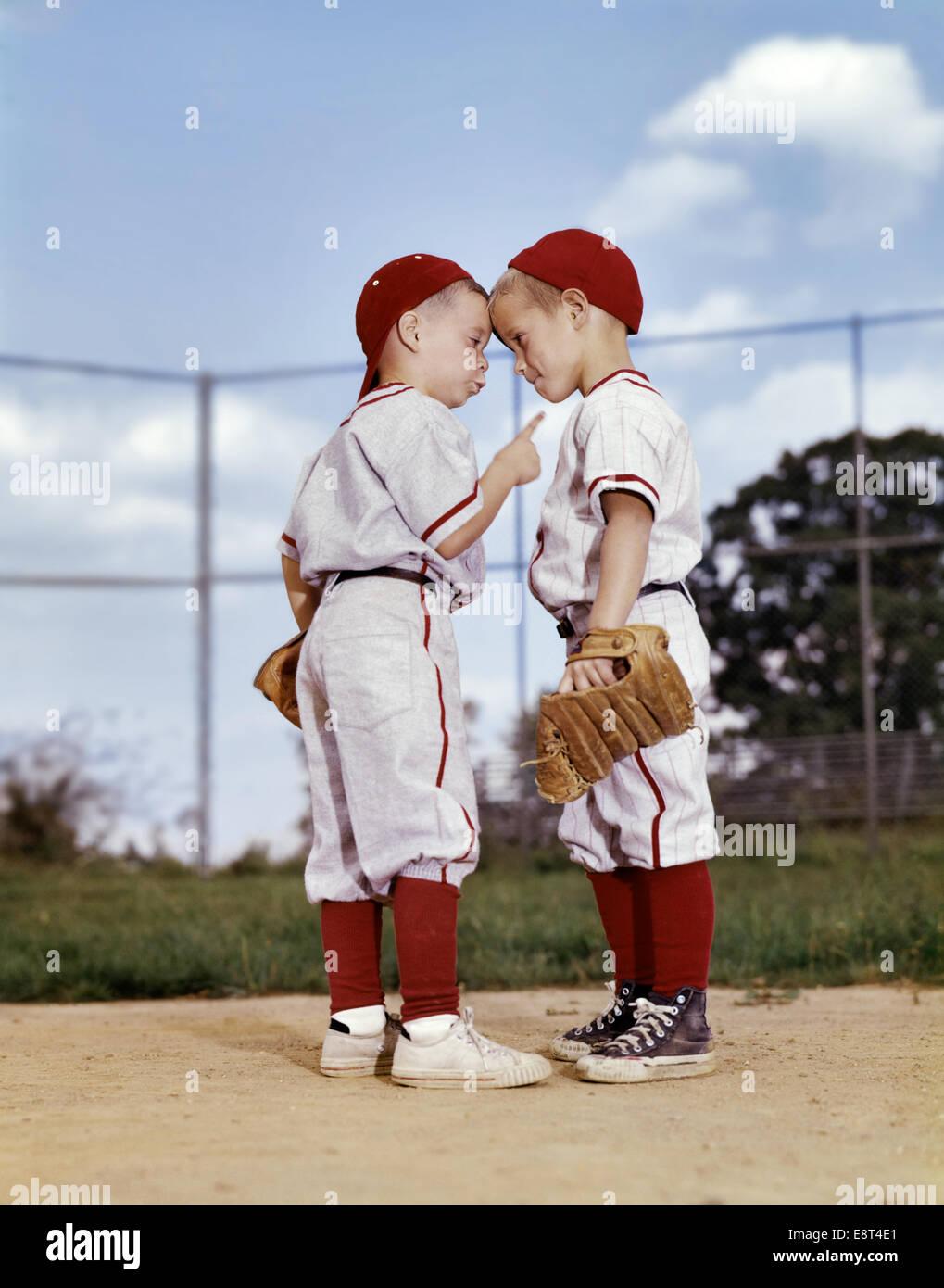 1960s TWO BOYS WEARING LITTLE LEAGUE BASEBALL UNIFORMS ...