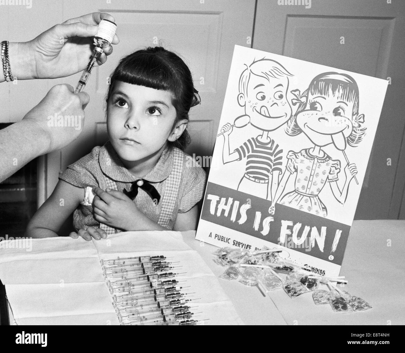 1950s LITTLE GIRL LOOKING UP ABOUT TO GET POLIO VACCINATION AT SCHOOL SIGN THIS IS FUN WITH LOLLIPOPS - Stock Image