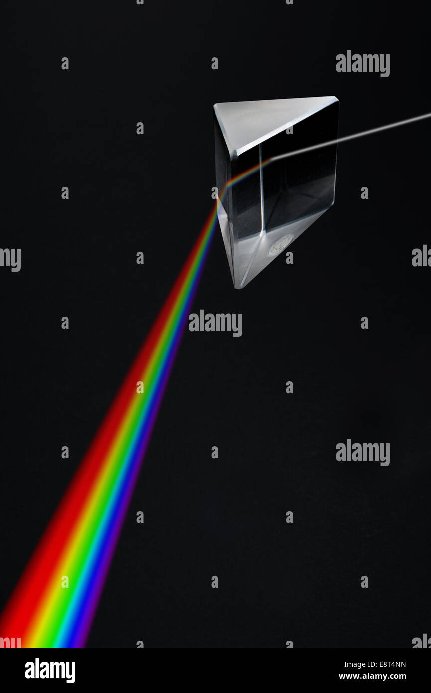 Light passing through a triangular highly polished prism broken up into colors of spectrum rainbow - Stock Image