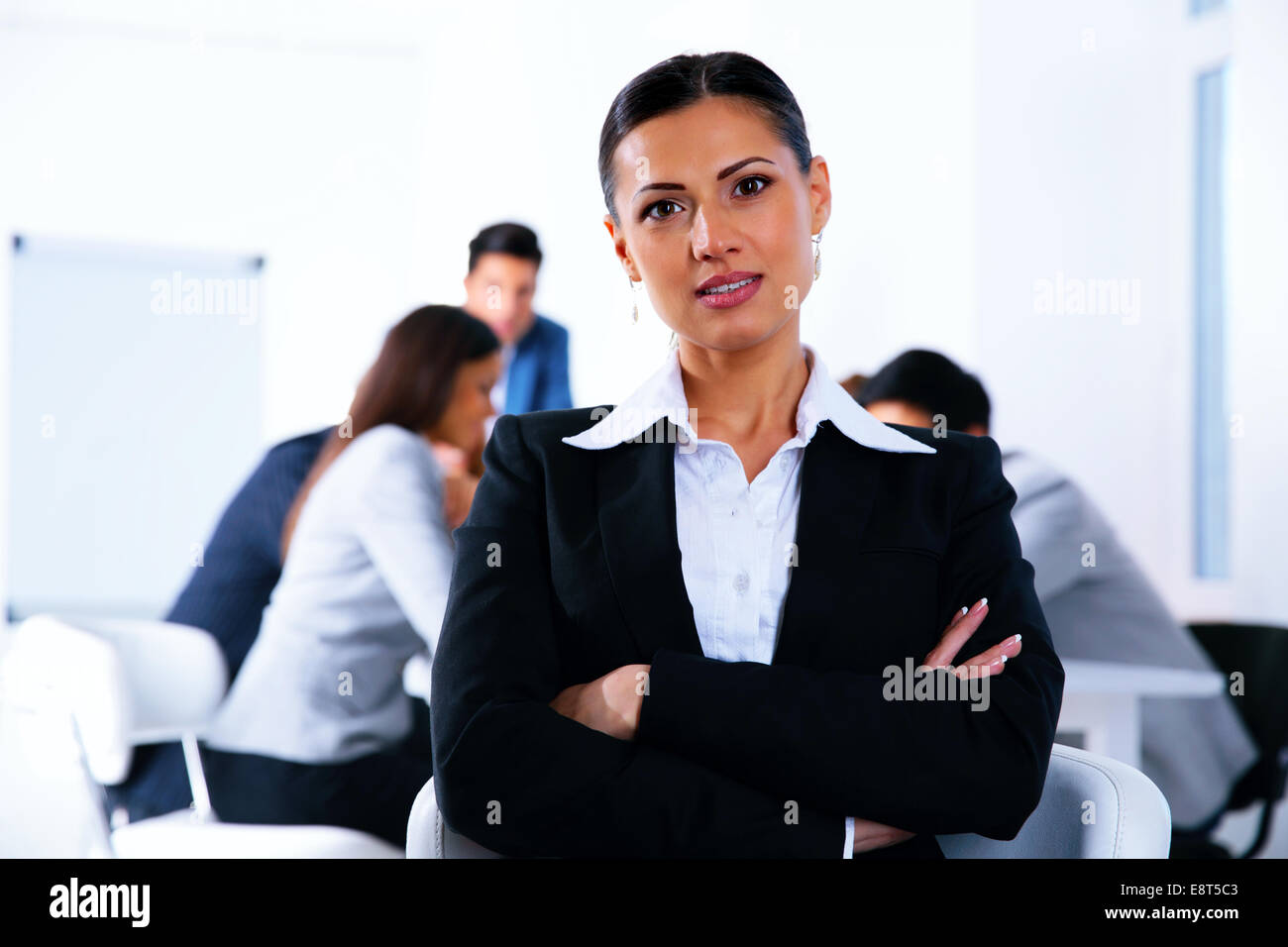 Businesswoman with arms folded standing in front of a metting - Stock Image