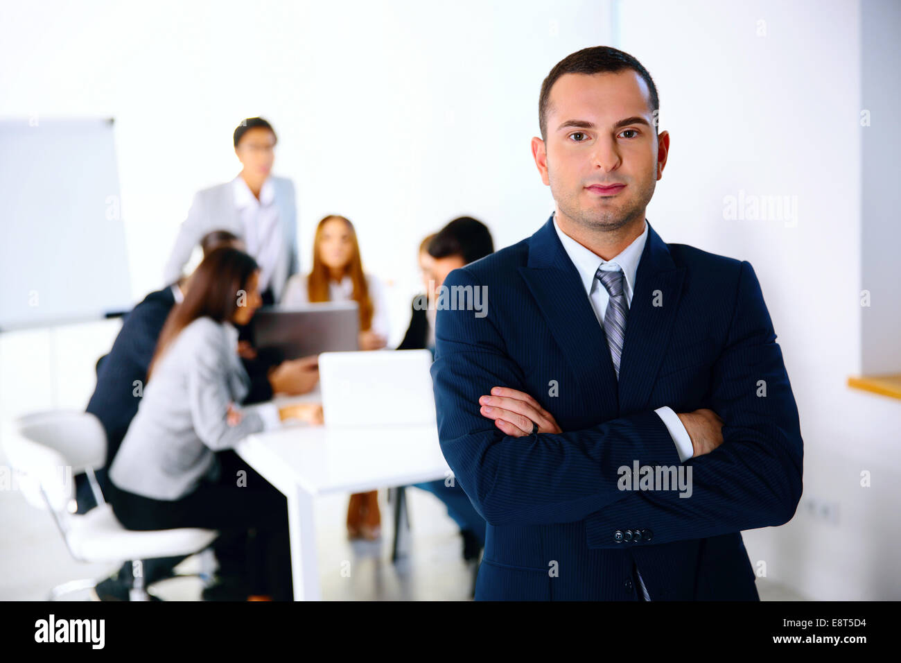 Portrait of a businessman standing in front of business meeting - Stock Image