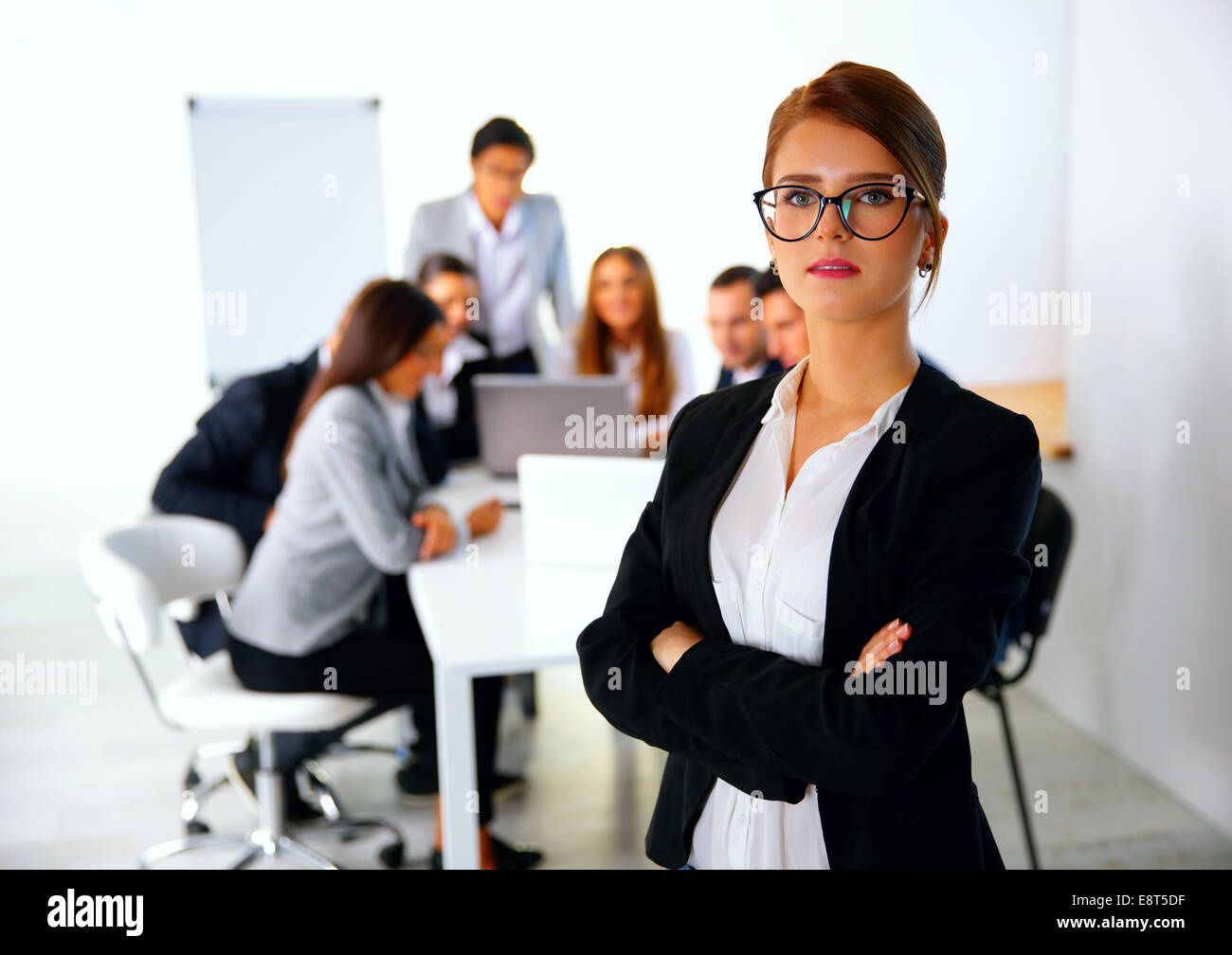 Portrait of a businesswoman standing in front of a business meeting - Stock Image