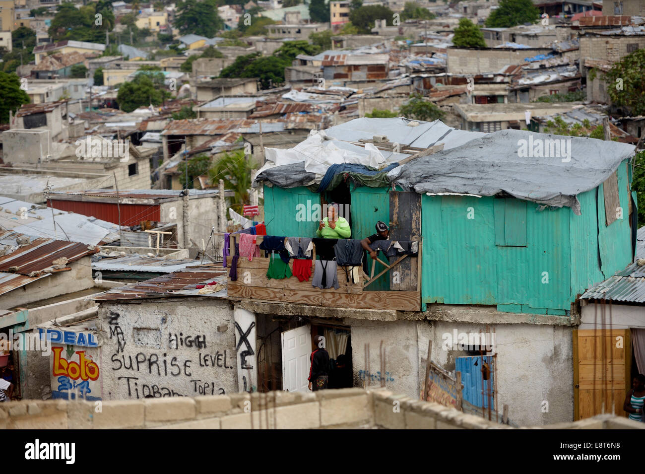 Woman on the balcony of her green-painted shack, Fort National slum, Port-au-Prince, Haiti - Stock Image