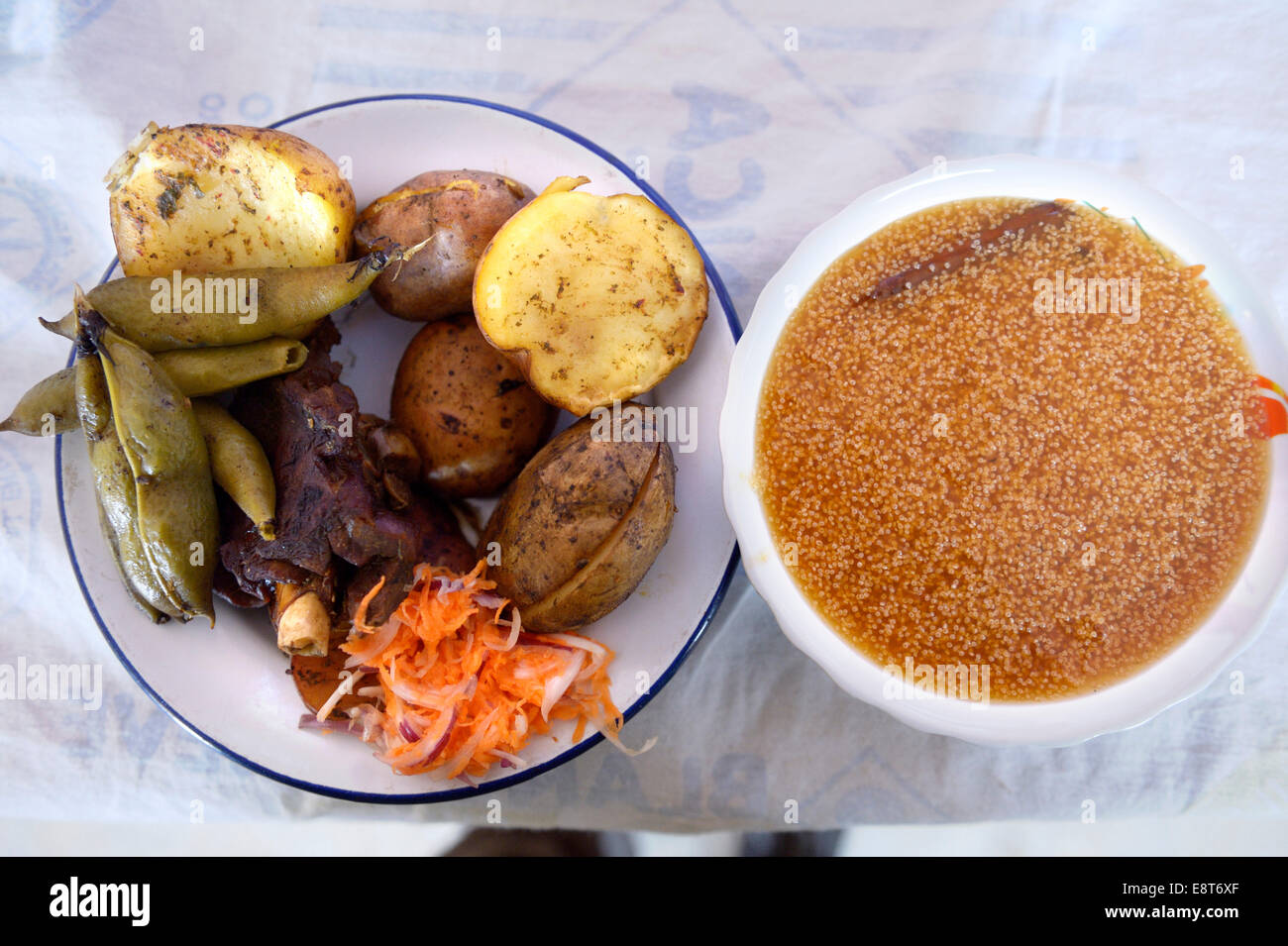 Traditional Andean cuisine, quinoa soup and a dish with potatoes, pork, Haba or broad beans and carrot salad, Chuquis - Stock Image