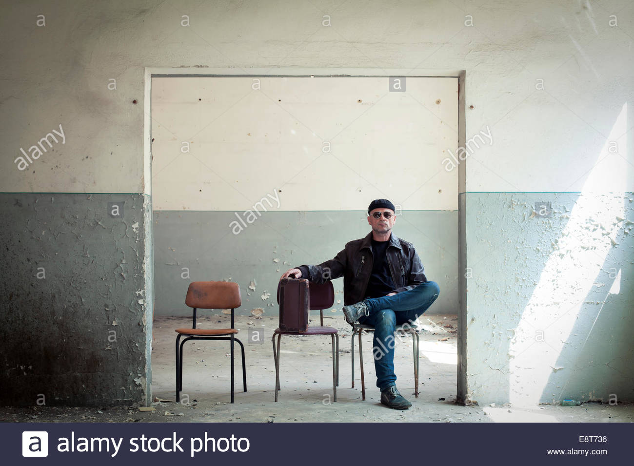 A traveller with a suitcase is sitting in an old building - Stock Image