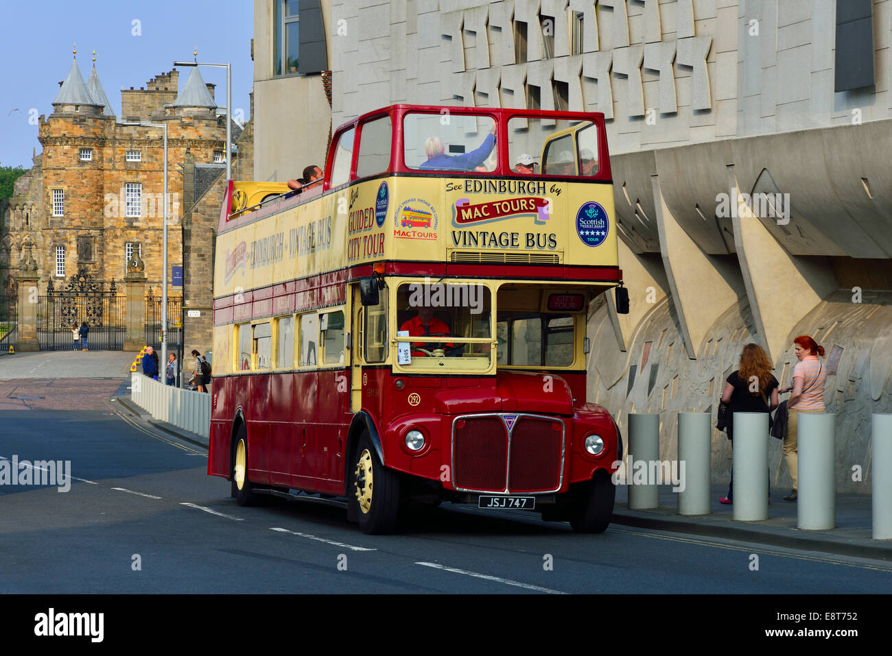 Tourist bus in front of the modern Scottish Parliament and the Holyrood Palace, Edinburgh, Scotland, United Kingdom - Stock Image