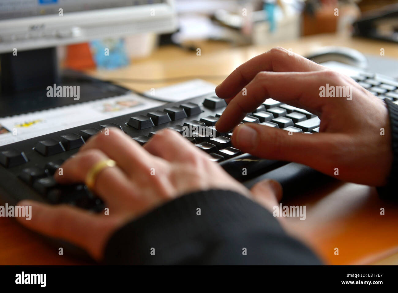 Hands typing on a computer keyboard - Stock Image