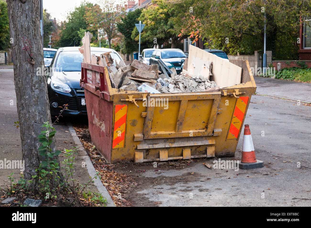 Skip with builder's waste on a residential road in Nottinghamshire, England, UK - Stock Image