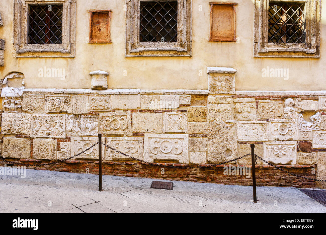 Roman or Etruscan reliefs on a the wall of Palazzo Bucelli in Montepulciano, Tuscany, Italy - Stock Image