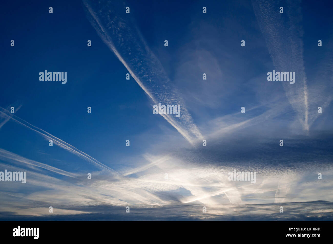 Small fluffy clouds, Cirrocumulus clouds, and medium-high stratus clouds, Altostratus, with contrails - Stock Image