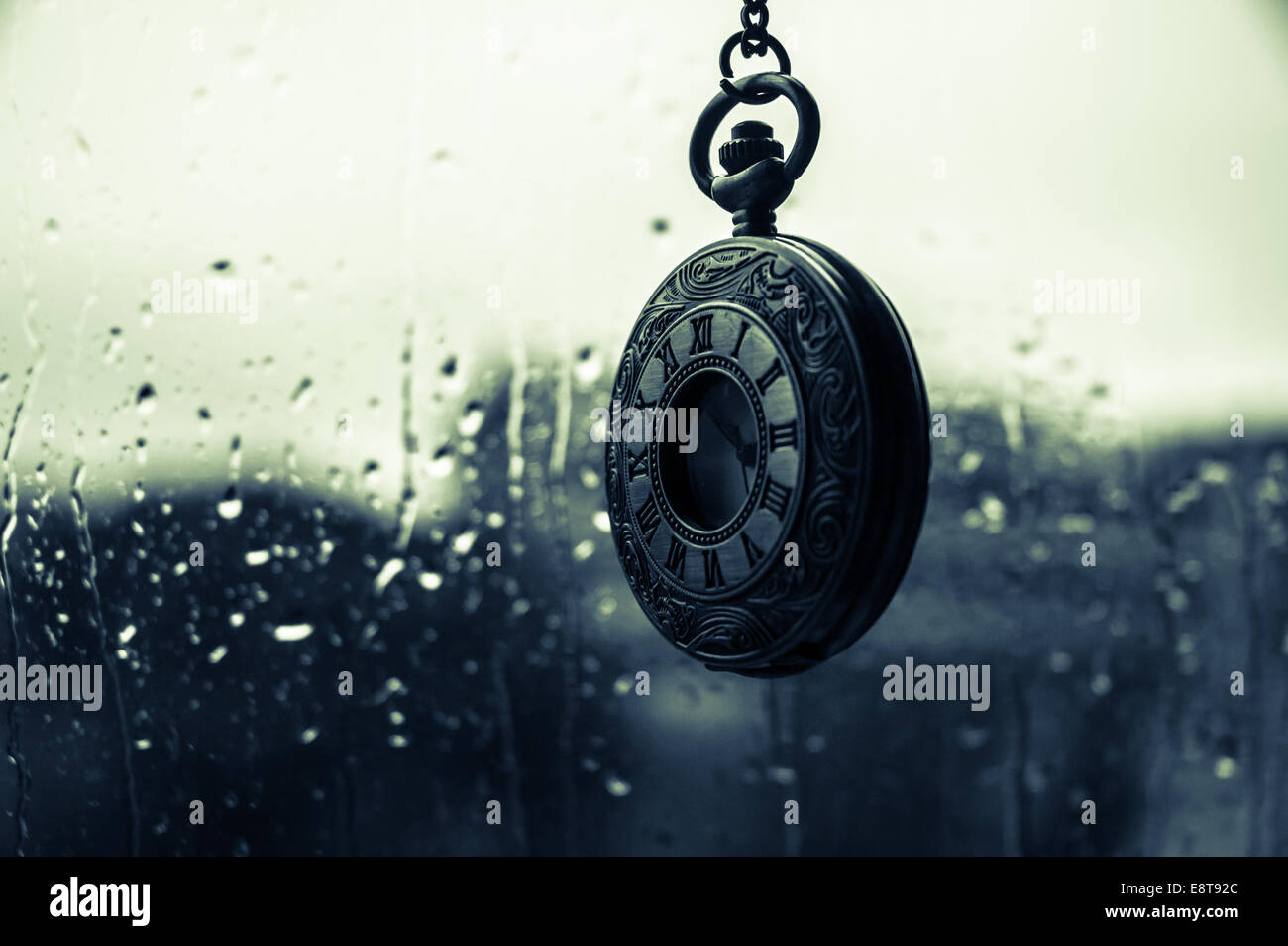 An old antique clock in the rain - Stock Image