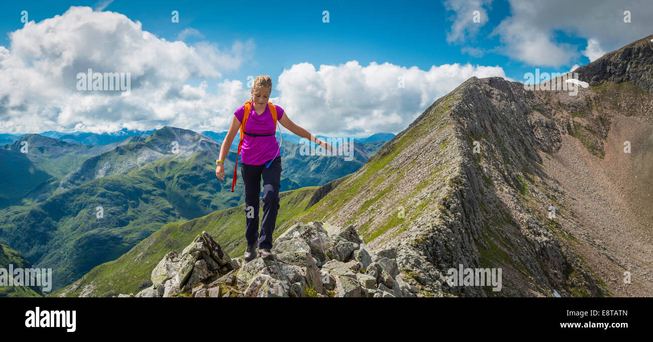 Caucasian girl hiking on rocky mountain - Stock Image