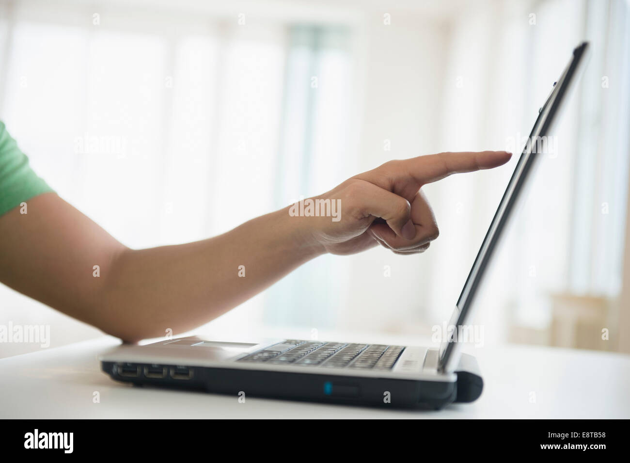 Mixed race man pointing to laptop screen Stock Photo