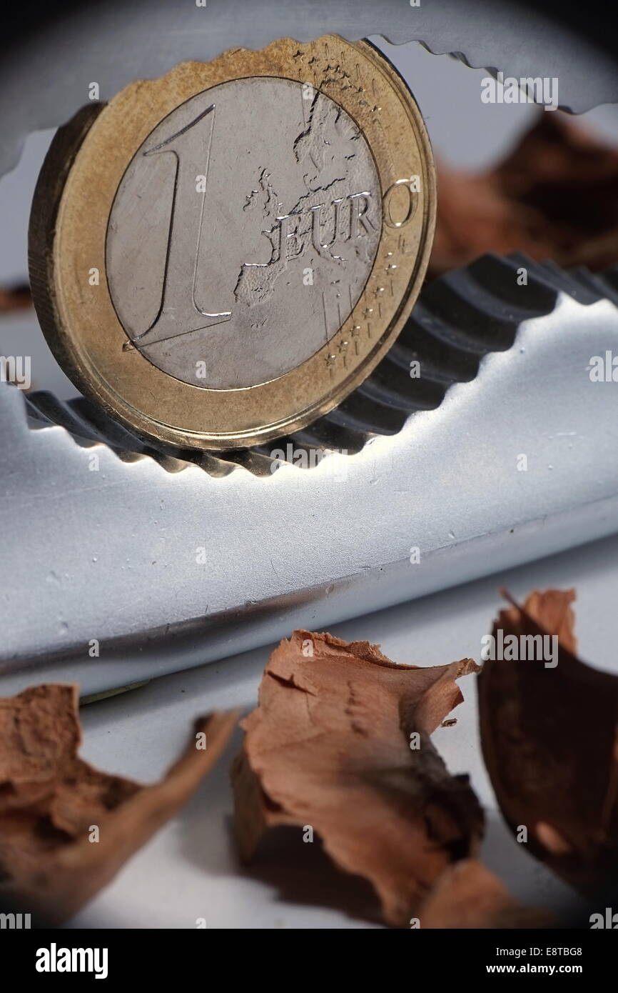 Close-up of one Euro breaking out of a nut by a nutcracker - Stock Image