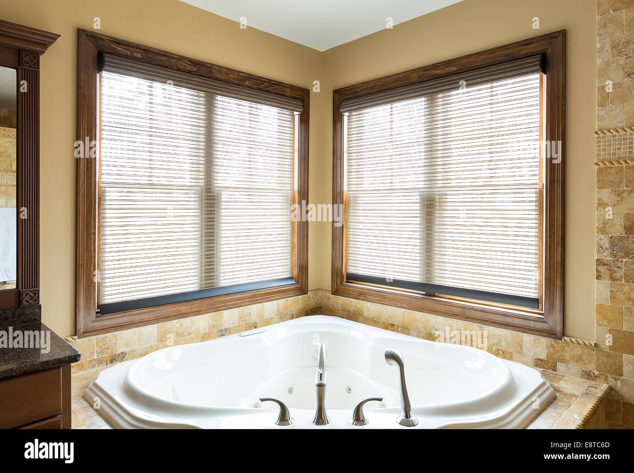 . Luxury bathtub and windows in corner of modern bathroom Stock Photo