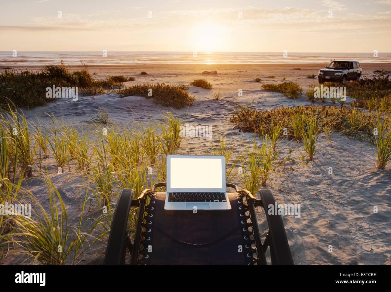 Laptop on deck chair overlooking sunset on beach - Stock Image