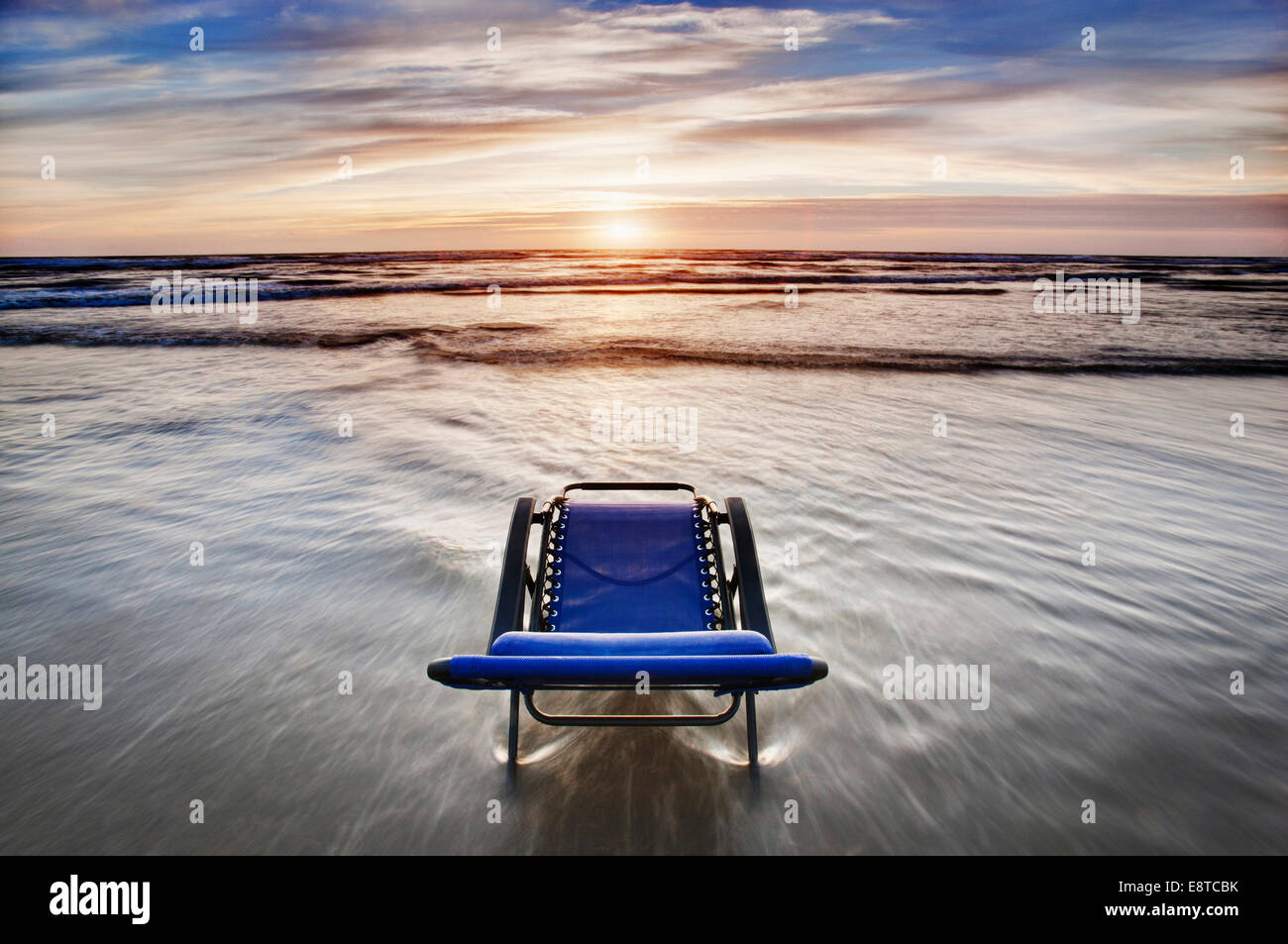 Deck chair overlooking sunset on beach - Stock Image