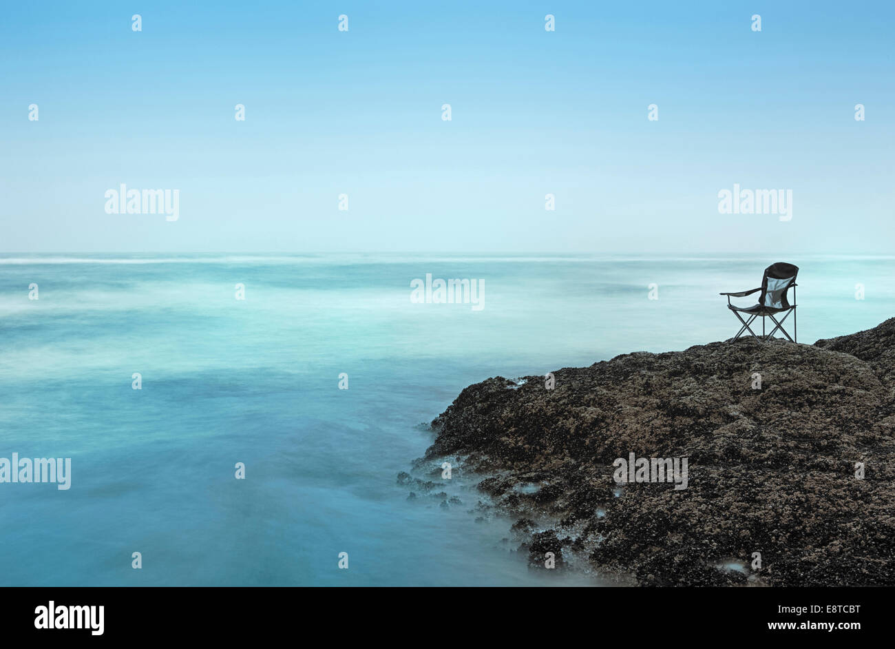 Chair overlooking waves on rocky beach - Stock Image