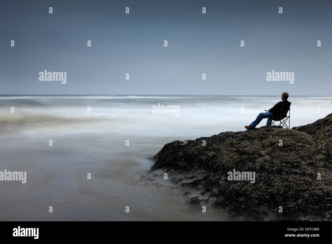 Caucasian man in chair overlooking waves on rocky beach - Stock Image
