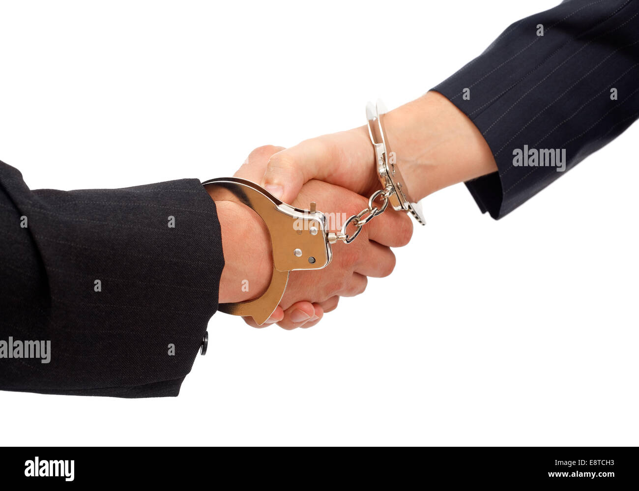 Forced handshake between two men, their hands linked with handcuffs - Stock Image