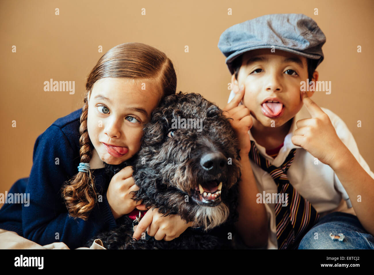 Mixed race children making faces with dog Stock Photo