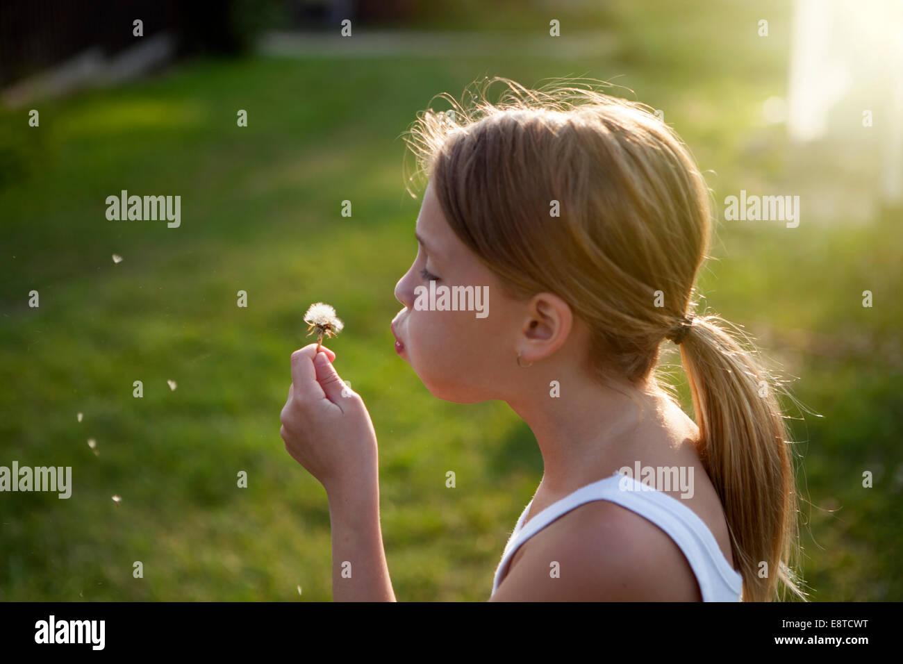 Caucasian girl blowing seeds off dandelion Stock Photo