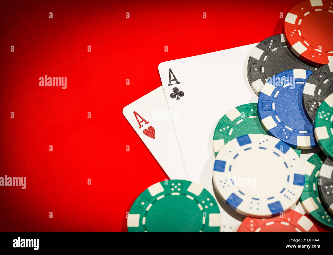 Pair of aces and chips on a red table - Stock Image