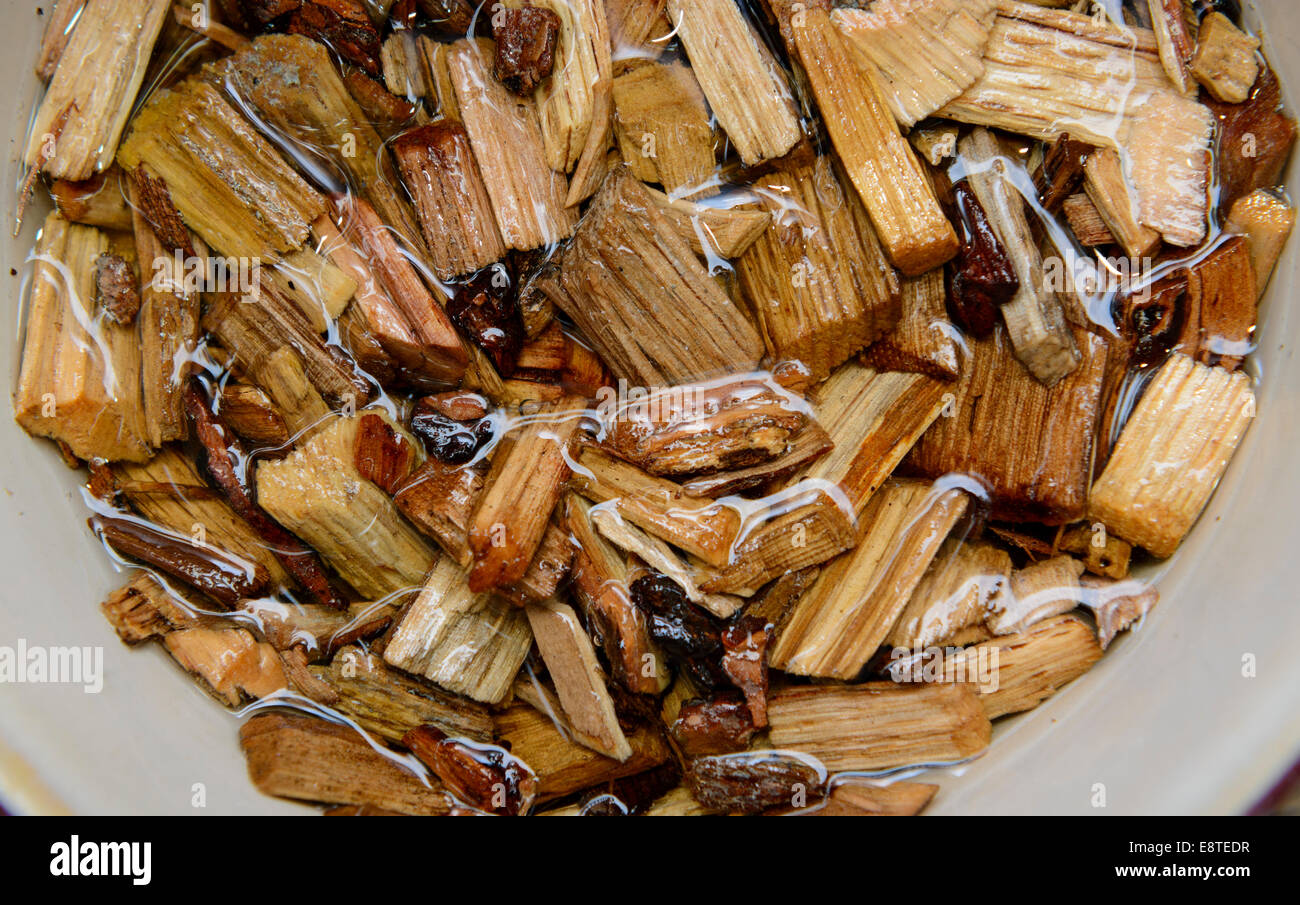 Hickory wood chips used to add flavorful smoke to barbecue are soaked in water before use. - Stock Image