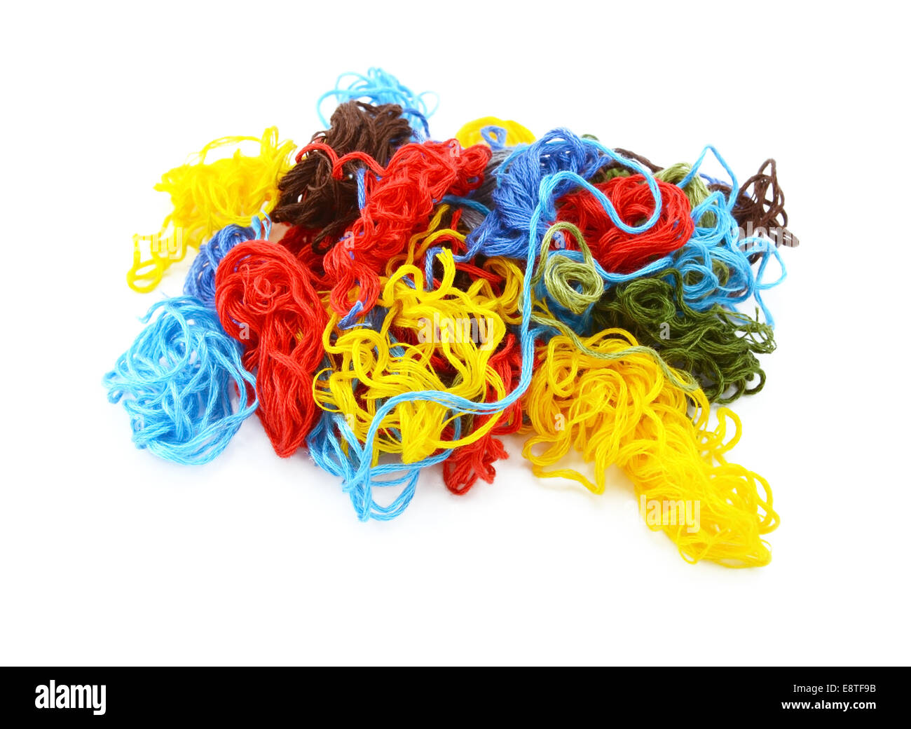 Multi-coloured embroidery threads in a tangled heap, isolated on a white background - Stock Image