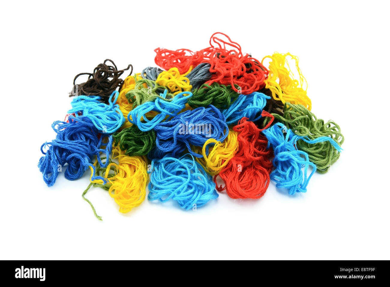 Assorted colourful embroidery threads in a heap, isolated on a white background - Stock Image