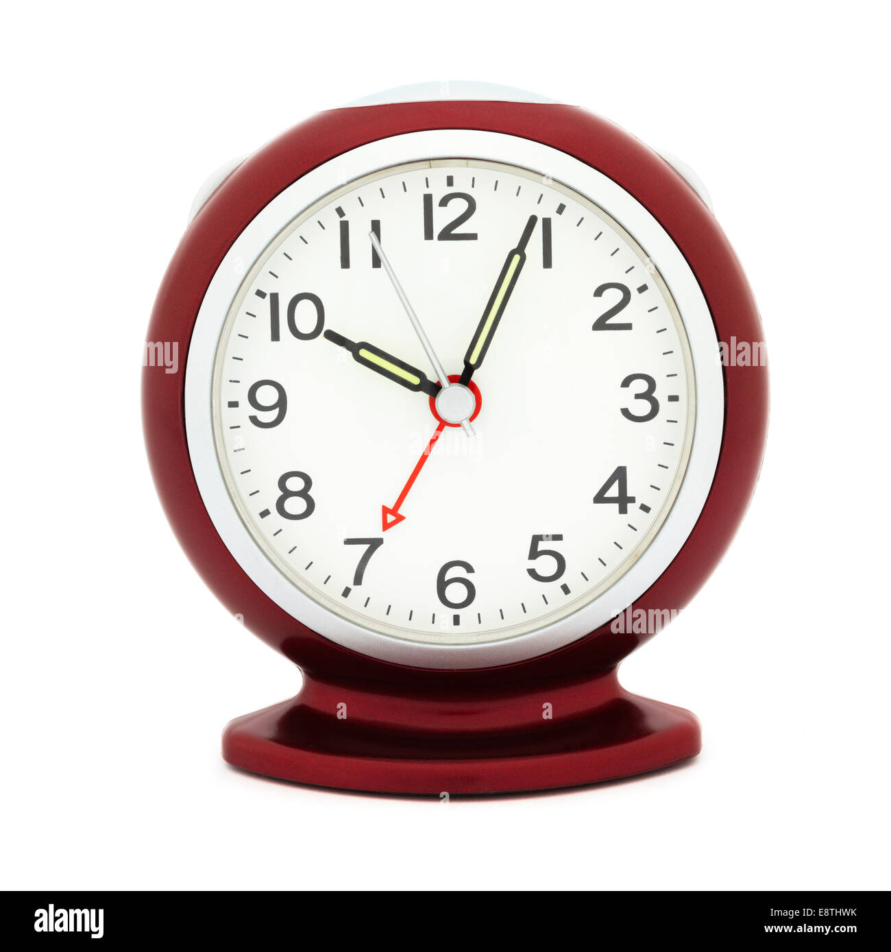 Red alarm clock with luminous hands after 10 am in a morning with alarm set at time 7 am to illustrate being late - Stock Image