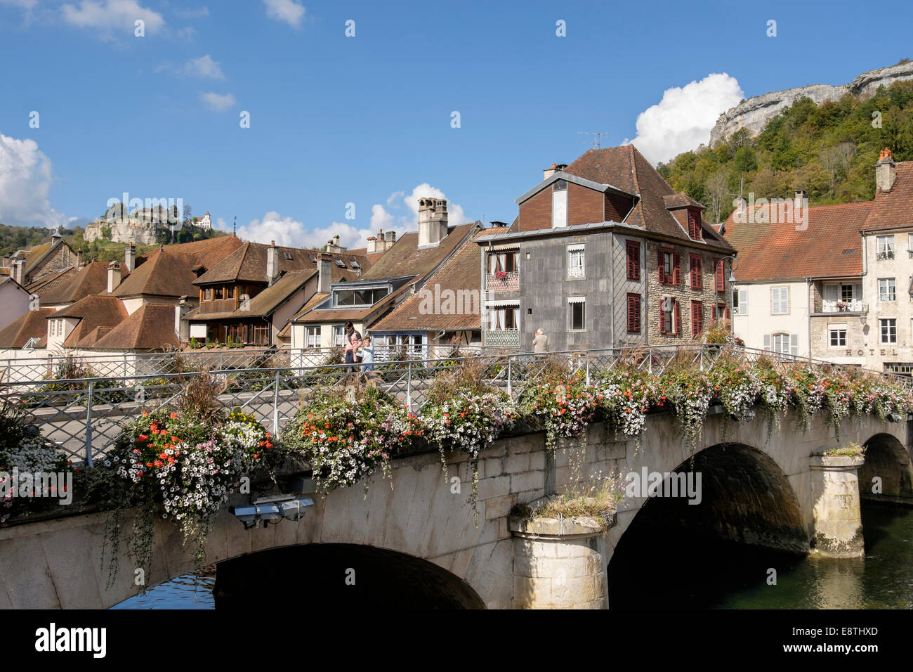 River Loue bridge with flowers and hilltop castle overlooking the town. Ornans, Doubs, Franche Comte, France, Europe - Stock Image