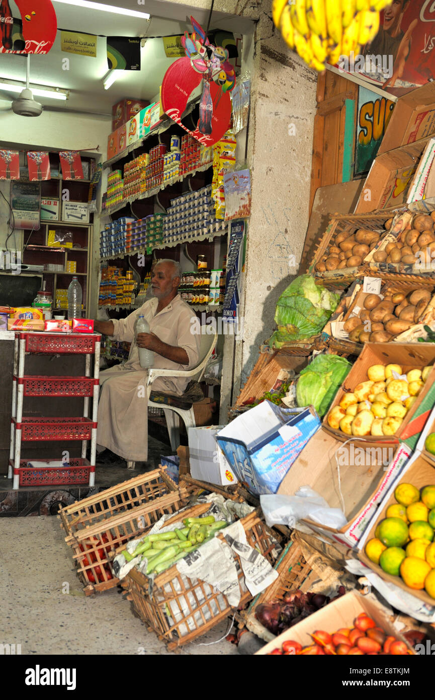 Egyptian shop keeper sitting inside his small food shop, Nuweiba, Egypt - Stock Image
