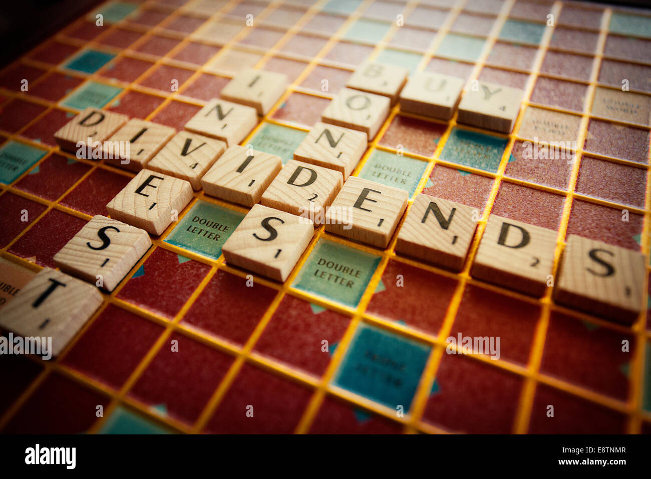 Financial terms spelled out on a Scrabble board - Stock Image