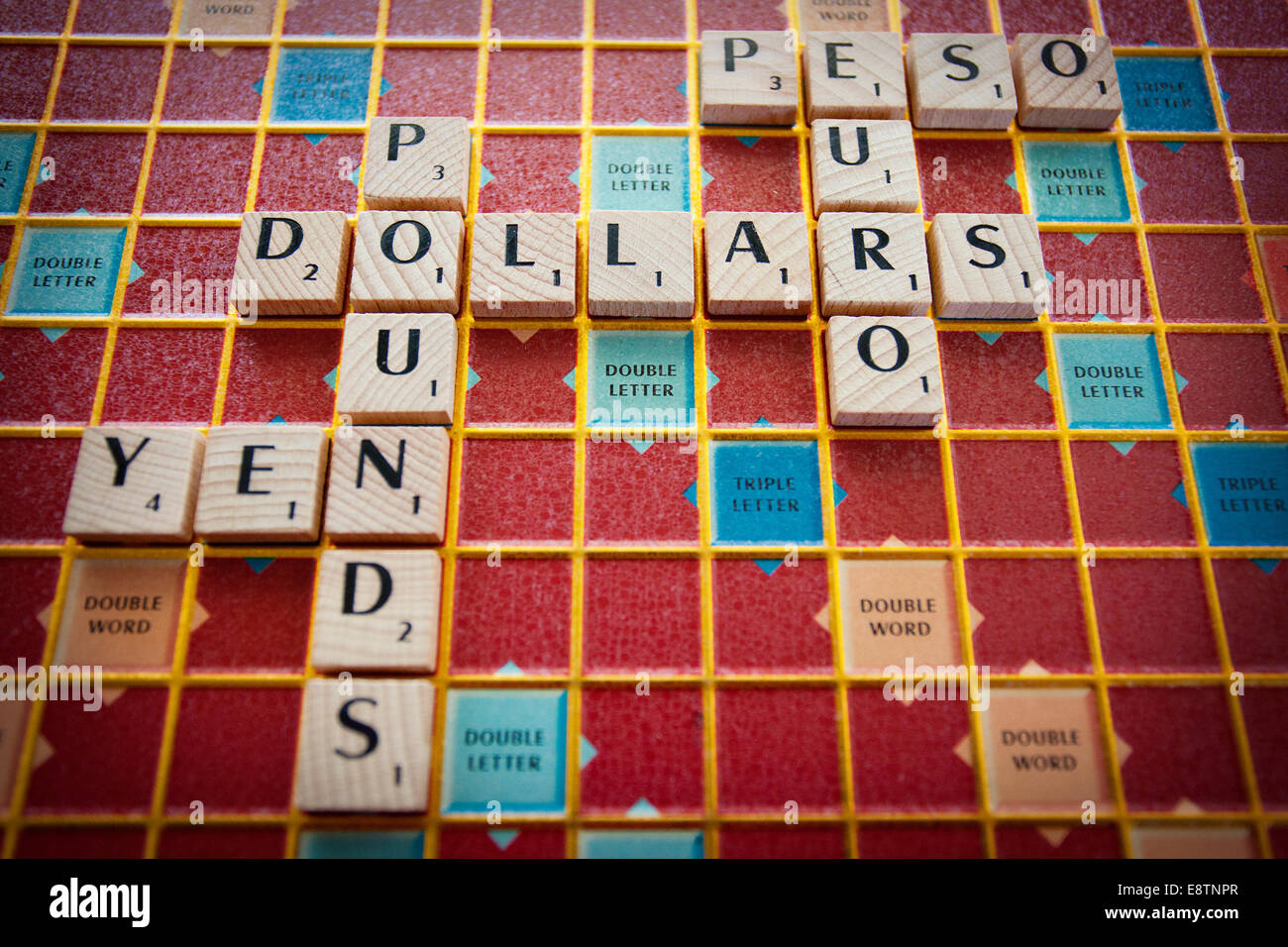 Various world currencies spelled out on a Scrabble board - Stock Image