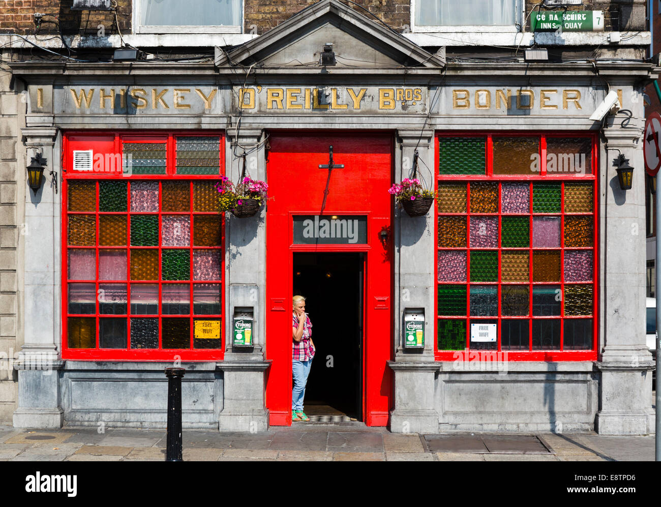 Woman smoking a cigarette in the doorway of a traditional pub on Inns Quay in the city centre, Dublin City, Republic - Stock Image